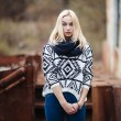 Young cute blonde woman in sweater, scarf, and jeans outdoors portrait with abandoned grunge background — Stock Photo #59326455