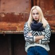 Young cute blonde woman in sweater, scarf, and jeans outdoors portrait with abandoned grunge background — Stock Photo #59326483