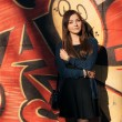 Outdoors portrait of a young beautiful brunette woman with long hair against an urban graffiti wall — Stock Photo #59928753