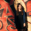 Outdoors portrait of a young beautiful brunette woman with long hair against an urban graffiti wall — Stock Photo #59928859