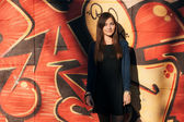 Outdoors portrait of a young beautiful brunette woman with long hair against an urban graffiti wall — Stock Photo