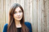 Closeup portrait of a young beautiful brunette woman with long hair against a wooden fence outdoors — Stock Photo