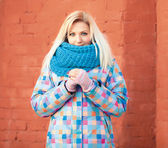 Naughty smiling beautiful blonde woman in bright jacket and scarf against a brick wall winter outdoors — Stock Photo