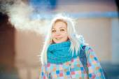Joyful naughty blonde woman in bright jacket and scarf exhales in winter city outdoors — Stockfoto