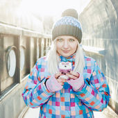 Smiling naughty blonde woman in bright jacket and hat with pompom texting on smartphone in sunny winter outdoors with the ships background — Stock Photo