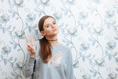 Lifestyle portrait of young hipster women posing indoor against a wall with a v gesture — Stock Photo