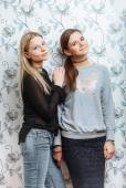 Lifestyle portrait of two young best friends hipster women posing against a wall — Stock Photo