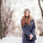 Winter portrait of a cute redhead lady in grey coat and scarf — Foto Stock