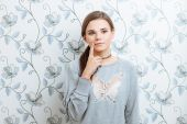Young hipster dreamy woman posing against wall with vintage wallpapers pattern — Stock Photo