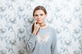 Young hipster dreamy woman against wall with vintage wallpapers pattern — Stock Photo