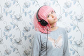 Young hipster woman in pink wig and dj headphones having fun against wall with vintage wallpapers pattern — Stock Photo