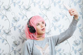 Young hipster woman in pink wig and dj headphones doing selfie against wall with vintage wallpapers pattern — Stock Photo
