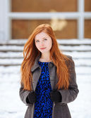 Emotive oortrait of young adorable redhead woman in blue dress and grey coat at winter outdoors — Stock Photo