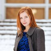 Closeup portrait of young adorable redhead woman in blue dress and grey coat at winter outdoors — Stock Photo