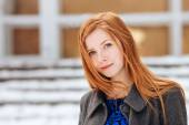 Closeup portrait of young cute redhead woman in blue dress and grey coat at winter outdoors — Stock Photo