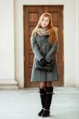 Full length portrait of young beautiful redhead woman wearing coat and scarf posing outdoors with architectural background — Stock Photo