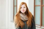 Young beautiful redhead woman wearing coat and scarf posing outdoors with architectural background — Stock Photo