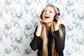 Portrait of young fashionable blonde woman enjoying music in big dj headphones indoors — 图库照片