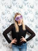 Portrait of young fashionable blonde woman posing in mask against a wall with vintage wallpapers pattern — Stock Photo