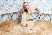Young beautiful blonde lady in vintage dress posing on the bed indoors — Stock Photo