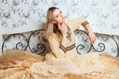 Young dreamy blonde woman sitting on the bed in vintage interior — Stock Photo
