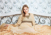 Young beautiful blonde woman in vintage dress posing on the bed indoor — Stock Photo