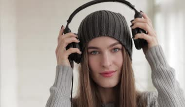 Young beautiful fashionable woman in big dj headphones phones enjoying music indoors — Stock Video