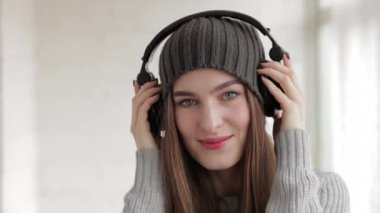 Young beautiful fashionable woman in big dj headphones phones enjoying music indoors — 图库视频影像