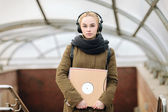 Young beautiful hipster woman in big dj headphones posing with a vinyl records on subway entrance — Stock Photo