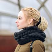 Closeup portrait of young beautiful blonde woman in olive parka with a dreadlocks bun hairstyle — Stock Photo