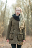 Young beautiful blonde hipster woman in scarf and parka with dreadlocks hairstyle posing on a blurry forest background — Stock Photo