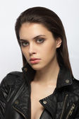 Emotive closeup portrait of a young fashionable brunette woman posing for model tests in black leather jacket — Stock Photo