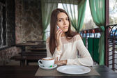 Young beautiful brunette woman answering a phone call in cafe terrace with a cappuccino cup — Stock Photo