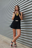 Full length portrait of stylish young beautiful hipster woman in little black dress drinking lemonade outdoors — Stock Photo