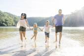 Family running on beach — Stock Photo