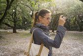 Girl makes photos in park — Stock Photo
