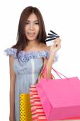 Beautiful Asian woman hold shopping bags show credit cards — Stock Photo
