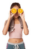 Asian healthy workout girl put orange over her eyes — Stock Photo