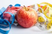 Measuring tape with red apple — Stock Photo