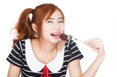 Happy Asian girl eat brownie — Stock Photo