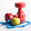 Red dumbbells weight with measuring tape and green apple — Stock Photo #56497575