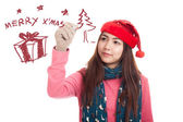 Asian girl with red christmas hat draw merry x' mas — Stock Photo