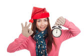 Asian girl with red christmas hat show OK and alarm clock — Stock fotografie