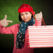 Asian girl with christmas hat point to shopping bag — Stock Photo #56686111