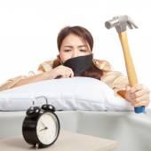 Sleepy Asian girl wake up hit alarm clock with hammer — Stock fotografie