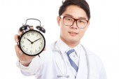 Asian male doctor show a clock — Stock Photo