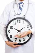 Asian male doctor show a clock and pills — Foto de Stock