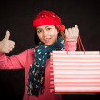 Asian girl  thumbs up with christmas hat and shopping bag — Stock Photo #57559989