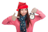 Asian girl with red christmas hat point to alarm clock — Stock fotografie