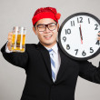 Happy Asian businessman with beer and clock at midnight — Stock Photo #57870155